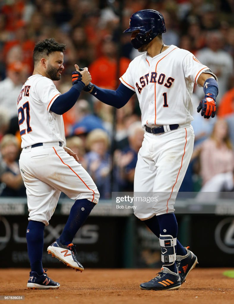 Carlos Correa #1 of the Houston Astros celebrates with Jose Altuve #27 after hitting a two run home run in the eighth inning against the Texas Rangers at Minute Maid Park on May 12, 2018 in Houston, Texas.