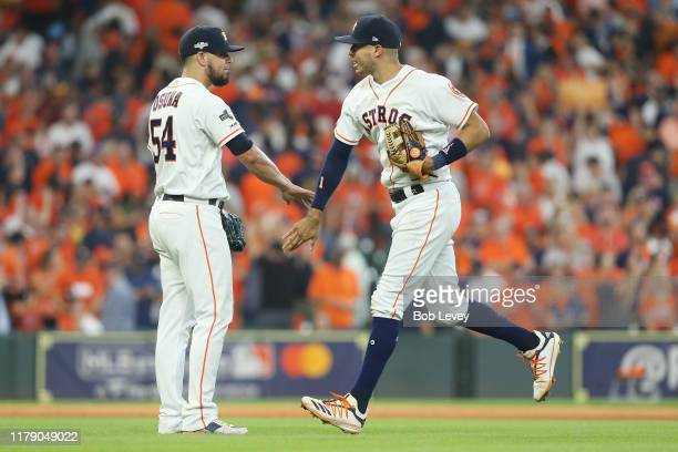 Carlos Correa of the Houston Astros celebrates with Roberto Osuna after defeating the Tampa Bay Rays 6-2 in game one of the American League Division...