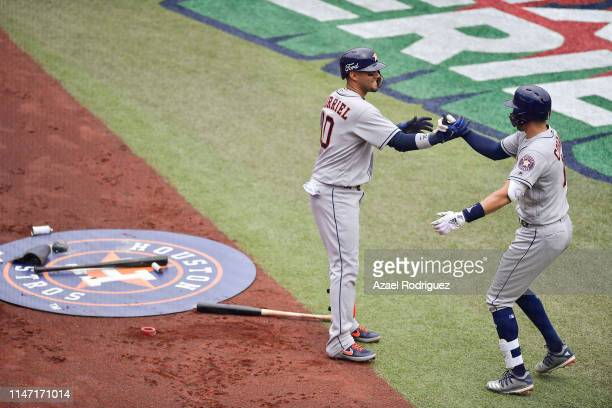 Carlos Correa of the Houston Astros celebrates with teammate Yuli Gurriel after hitting a home run and producing two runs on the second inning of the...