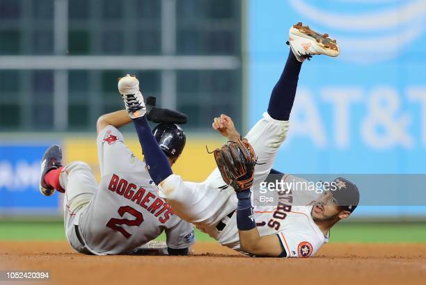 Carlos Correa of the Houston Astros collides with Xander Bogaerts of the Boston Red Sox at second base during a double play attempt in the seventh...