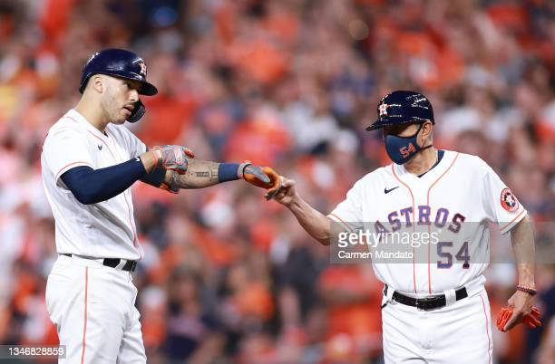 Carlos Correa of the Houston Astros fist bumps first base coach Dan Firova after he hit a single in the fifth inning against the Boston Red Sox...