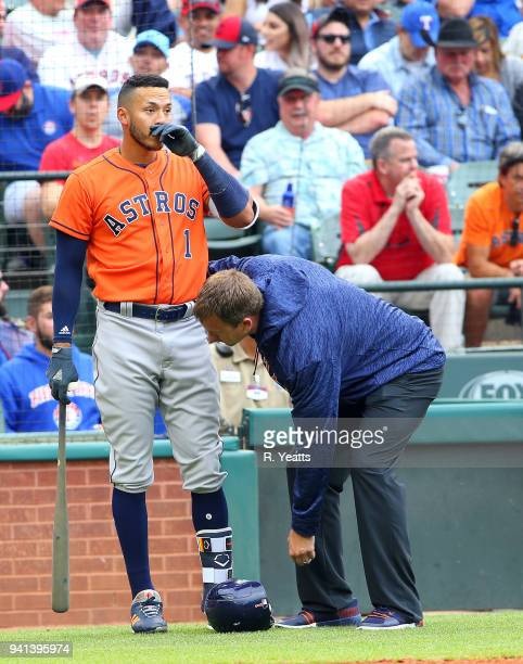 Carlos Correa of the Houston Astros is checked by the trainer after a foul tip hit is foot in the fifth inning against the Texas Rangers at Globe...