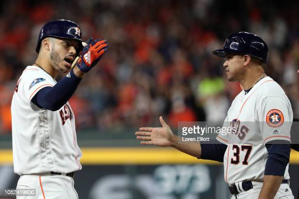 Carlos Correa of the Houston Astros is congratulated by first base coach Alex Cintron after hitting an RBI single in the fifth inning during Game 4...