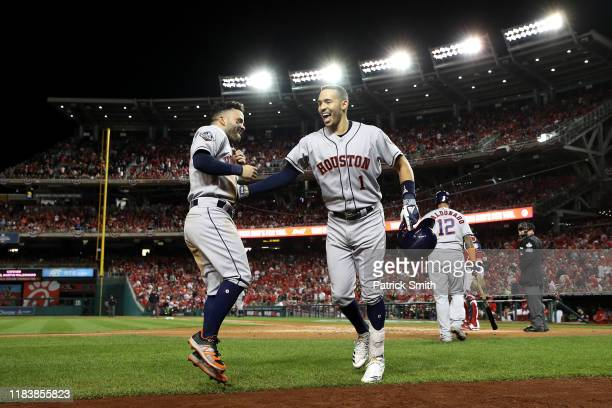 Carlos Correa of the Houston Astros is congratulated by his teammate Jose Altuve after hitting a two-run home run against the Washington Nationals...