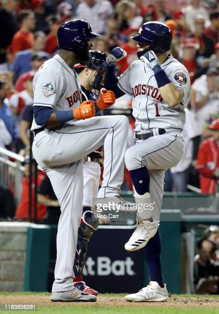 Carlos Correa of the Houston Astros is congratulated by his teammate Yordan Alvarez after hitting a tworun home run against the Washington Nationals...