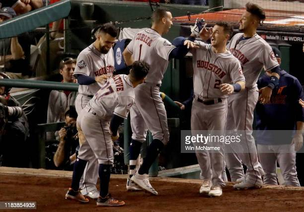 Carlos Correa of the Houston Astros is congratulated by his teammates after hitting a two-run home run against the Washington Nationals during the...