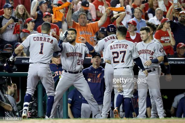 Carlos Correa of the Houston Astros is congratulated by his teammates after hitting a tworun home run against the Washington Nationals during the...