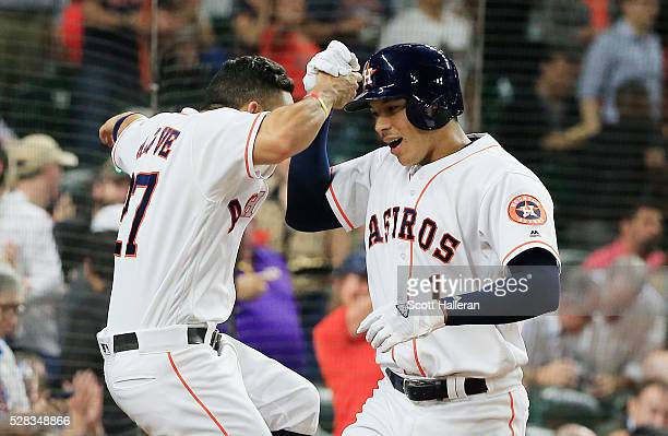 Carlos Correa of the Houston Astros is greeted by Jose Altuve after Correa hit a solo home run in the fourth inning off Casey Fien of the Minnesota...