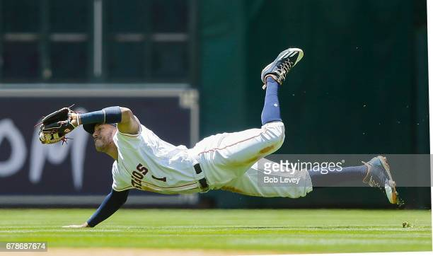 Carlos Correa of the Houston Astros makes a diving catch on a pop fly by Nomar Mazara of the Texas Rangers in the fourth inning at Minute Maid Park...
