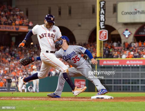 Carlos Correa of the Houston Astros reaches first as Cody Bellinger of the Los Angeles Dodgers is unable to make the catch in the fifth inning of...