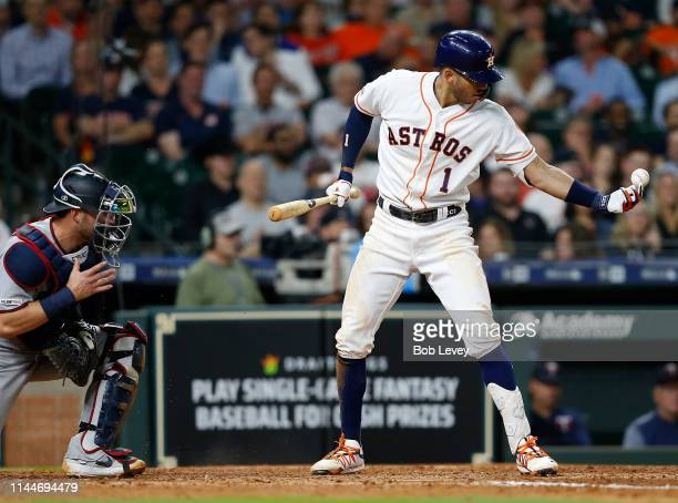 Carlos Correa of the Houston Astros reaches for a ball that was deemed in play and subsequently called out for batter interference in the seventh...