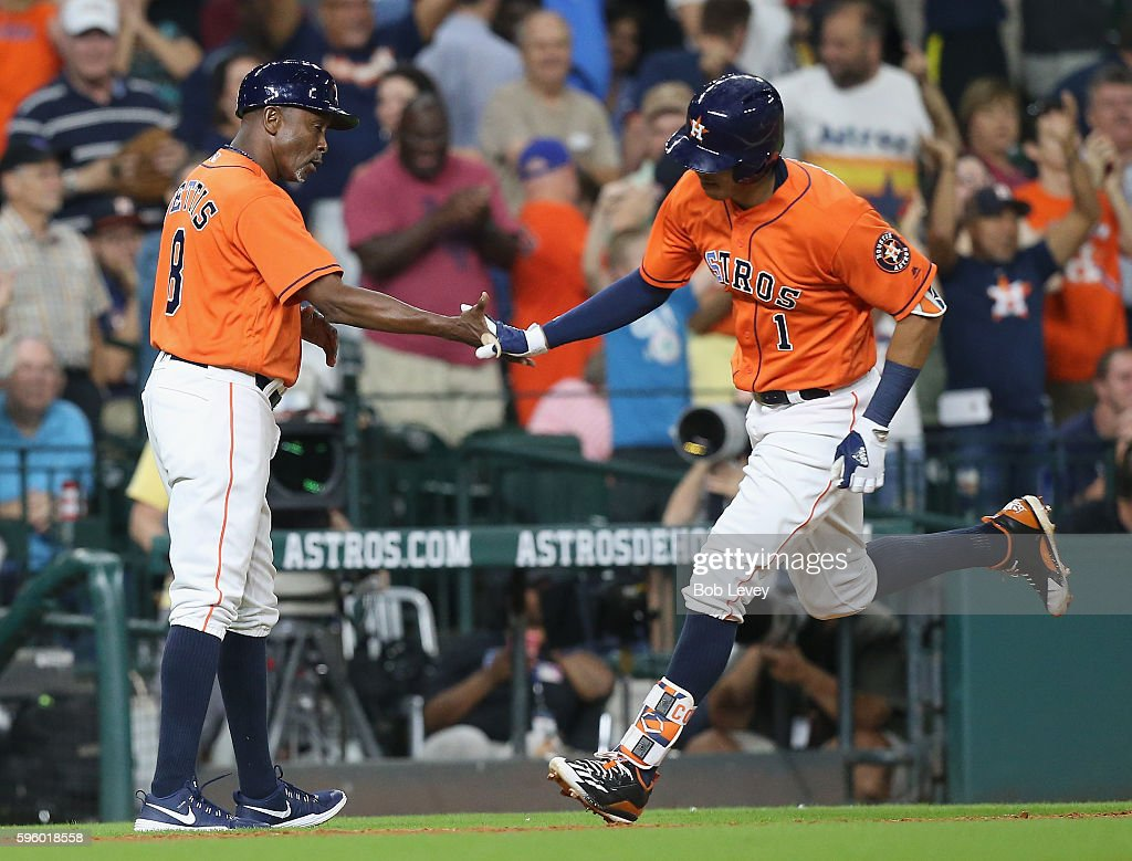 Carlos Correa #1 of the Houston Astros receives congratulations from third base coach Gary Pettis #8 after hitting a home run in the ninth inning at Minute Maid Park on August 26, 2016 in Houston, Texas.