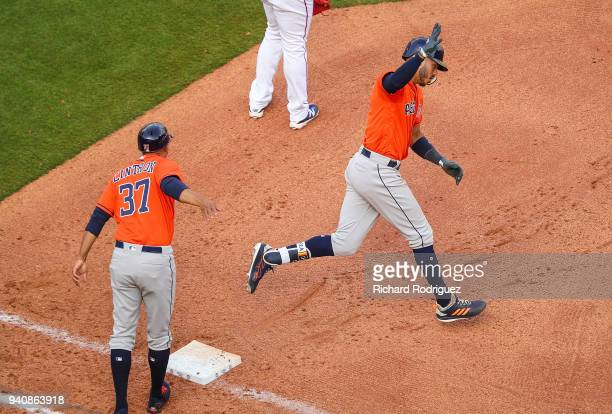 Carlos Correa of the Houston Astros rounds first base past Alex Cintron of the Houston Astros after a two run home run against the Texas Rangers in...