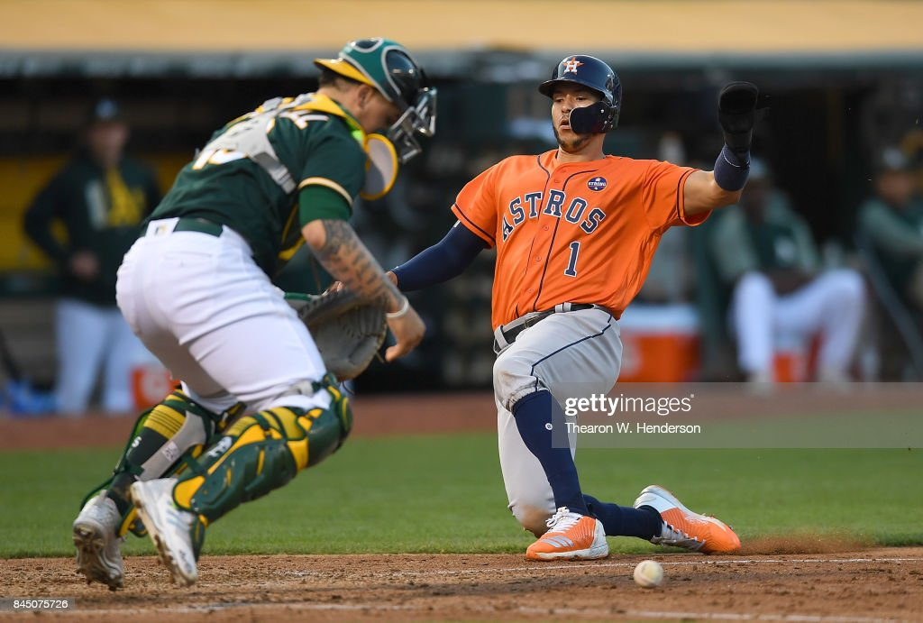 Carlos Correa #1 of the Houston Astros scores as catcher Bruce Maxwell #13 of the Oakland Athletics can't handle the throw in the top of the six inning of the second game in a double header at Oakland Alameda Coliseum on September 9, 2017 in Oakland, California.