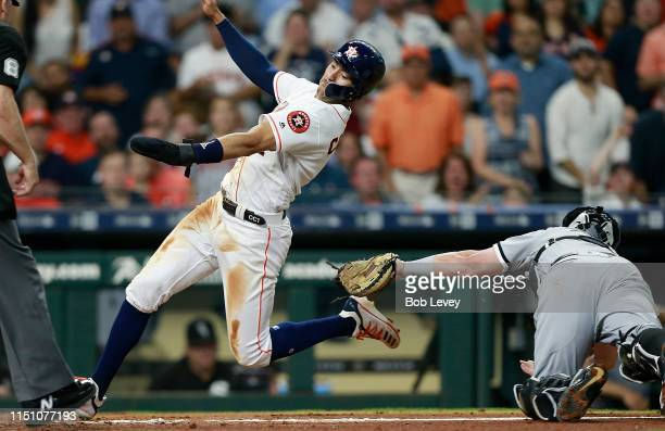 Carlos Correa of the Houston Astros scores in the fourth inning as he avoids the tag of catcher James McCann of the Chicago White Sox at Minute Maid...