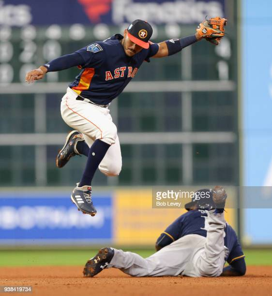 Carlos Correa of the Houston Astros tags out Domingo Santana of the Milwaukee Brewers trying to steal second in the fourth inning during a spring...