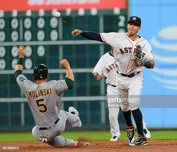 Carlos Correa of the Houston Astros throws over Jake Smolinski of the Oakland Athletics to complete a double play in the third inning at Minute Maid...
