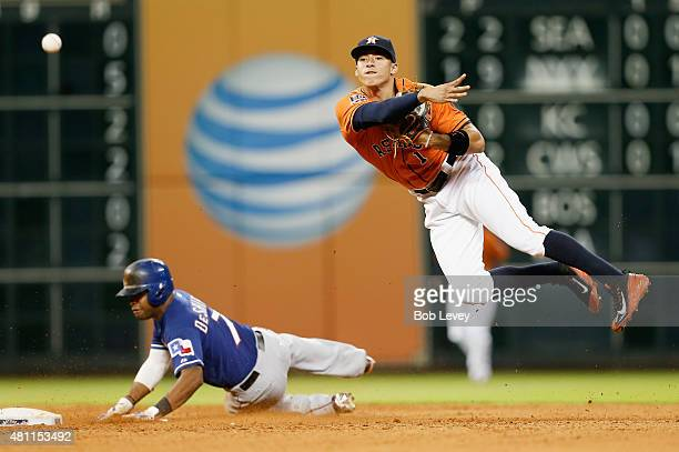 Carlos Correa of the Houston Astros throws to first base over a sliding Delino DeShields of the Texas Rangers in the fifth inning at Minute Maid Park...