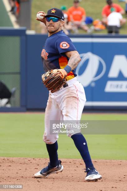 Carlos Correa of the Houston Astros turns the double play on a ball hit by Frank Schwindel the Detroit Tigers during a spring training game at the...
