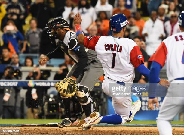 Carlos Correa of the Puerto Rico scores the winning run against catcher Shawn Zarraga of the Netherlands in the 11th inning during Game 1 of the...