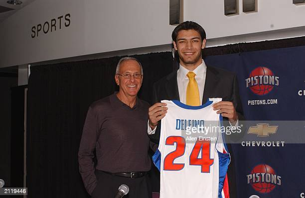 Carlos Delfino 25th pick of the 2003 NBA draft holds his new uniform with Detroit Pistons coach Larry Brown at the Palace of Auburn Hills June 27...