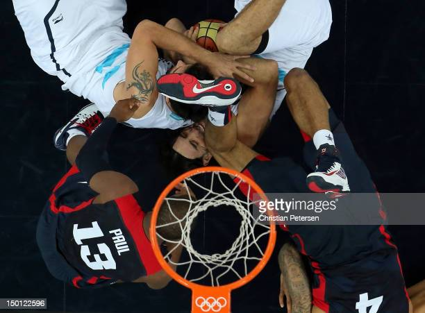 Carlos Delfino and Luis Scola of Argentina battle for the ball under the basket with Chris Paul and Tyson Chandler of United States in the third...
