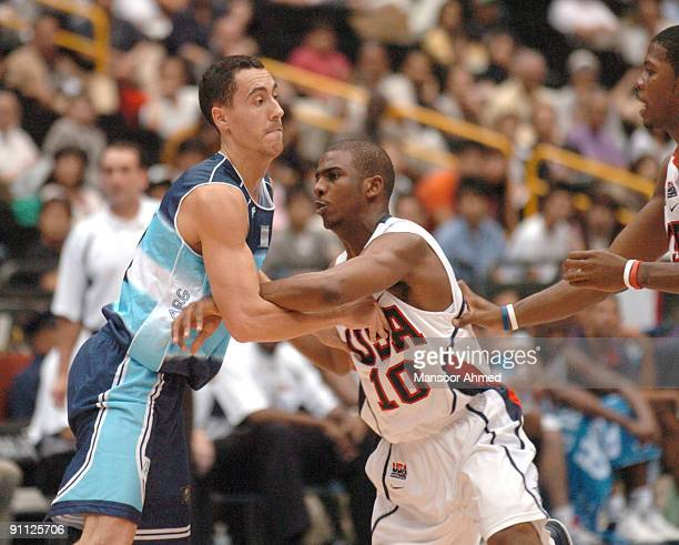 Carlos Delfino of Argentina and Team USA's Chris Paul grab onto one another during the Bronze Medal game at the FIBA World Championship 2006 at the...