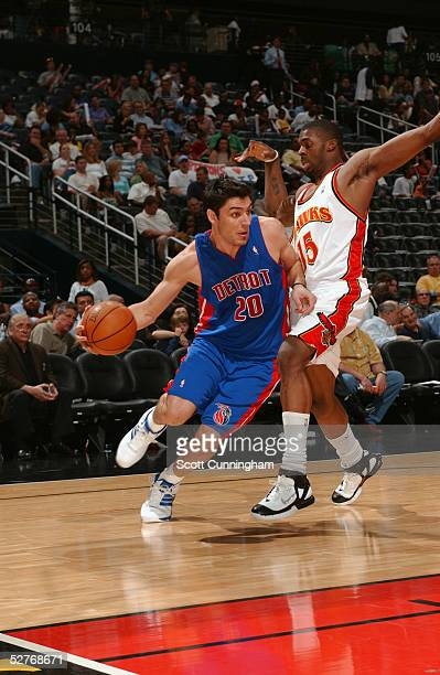 Carlos Delfino of the Detroit Pistons drives around Donta Smith of the Atlanta Hawks during the game at Philips Arena on April 19 2004 in Atlanta...