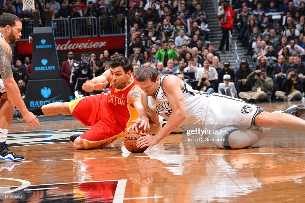 Carlos Delfino #10 of the Houston Rockets and Mirza Teletovic #33 of the Brooklyn Nets reach for the ball at the Barclays Center on February 22, 2013 in Brooklyn, New York.