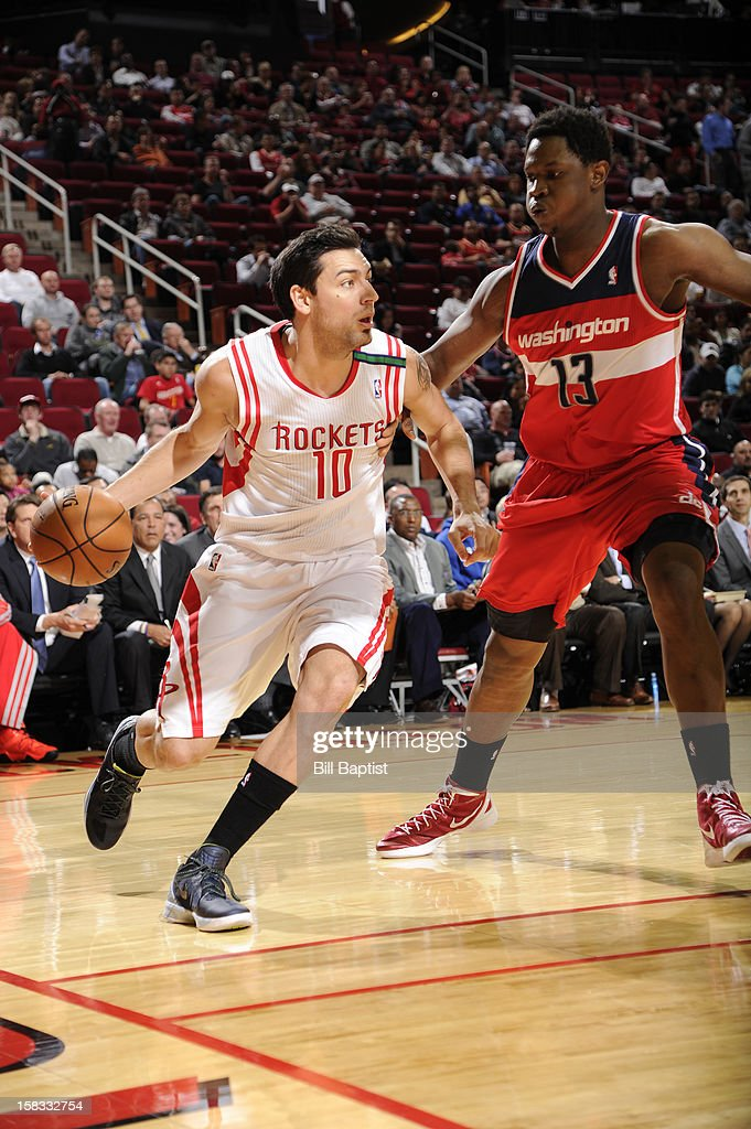 Carlos Delfino #10 of the Houston Rockets drives baseline against the Kevin Seraphin #13 of the Washington Wizards on December 12, 2012 at the Toyota Center in Houston, Texas.