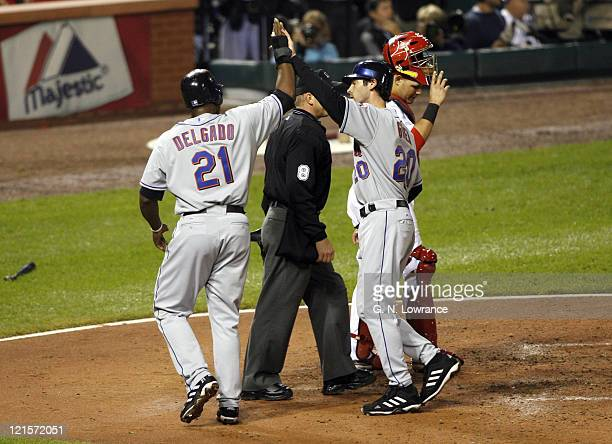 Carlos Delgado and Shawn Green of the Mets score in the 4th inning on a double by Jose Valentine during game 5 action of the NLCS between the New...