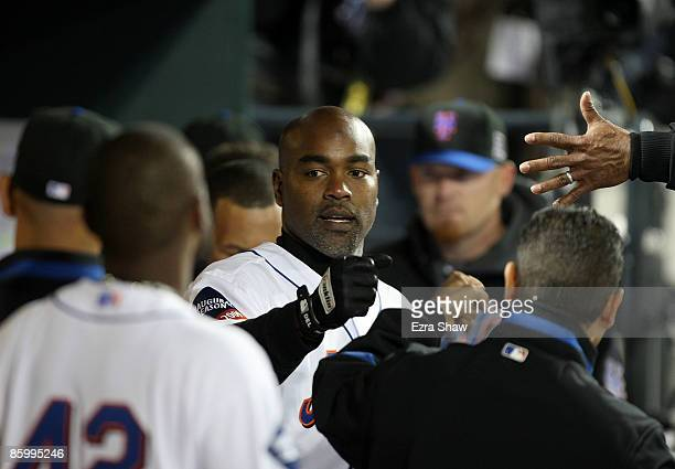 Carlos Delgado of the New York Mets is congratulated by teammates in the dugout after he hit a solo home run in the eighth inning of their game...