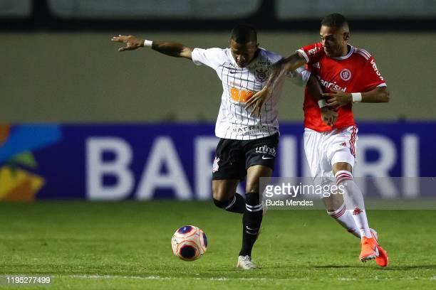 Carlos Eduardo of Internacional struggles for the ball with Leo Pereira of Corinthians during a match between Internacional and Corinthians as part...