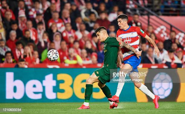 Carlos Fernandez of Granada competes for the ball with Yuri Berchiche of Athletic Bilbao during the Copa del Rey Semi Final second leg match between...