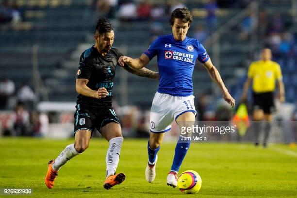 Carlos Fierro of Cruz Azul drives the ball while followed by Luis Noriega of Puebla during the 10th round match between Cruz Azul and Queretaro as...