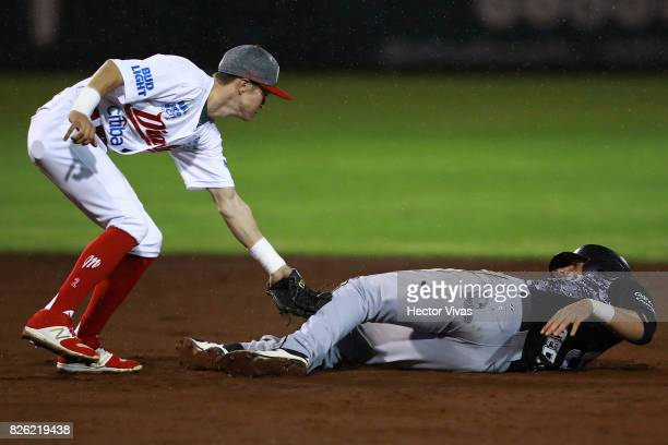 Carlos Figueroa of Diablos Rojos tagged out Alex Liddi of Toros de Tijuana on second base during the match between Toros de Tijuana and Diablos Rojos...