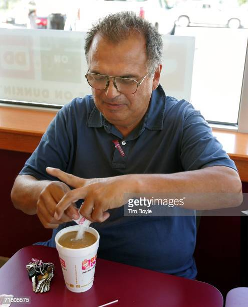 Carlos Garcia pours sugar into a cup of coffee at a Dunkin' Donuts store September 7 2006 in Chicago Illinois In an effort to compete with Starbucks...