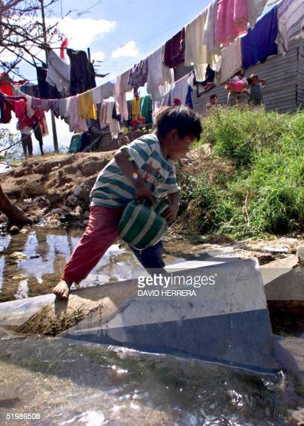 Carlos gathers water for his family 23 December 2001 in front of their home in Guatemala City Carlos and his family are facing Christmas this year in...