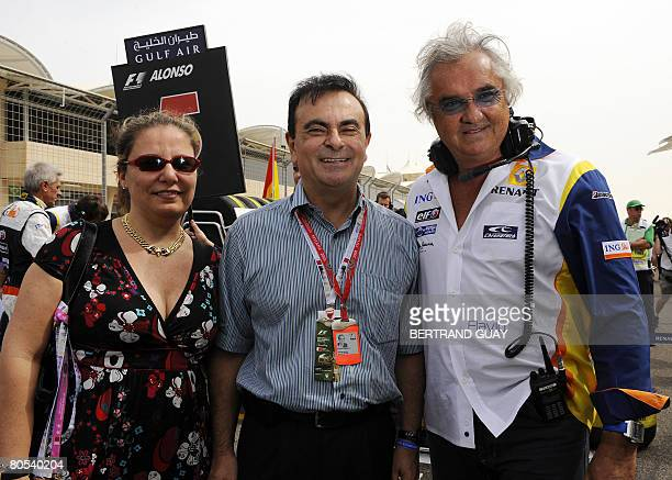 Carlos Ghosn CEO of Renault and Nissan and his wife Rita pose with Renault's team chief Flafio Briatore in the starting grid of the Sakhir racetrack...