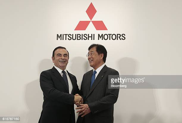 Carlos Ghosn chairman and chief executive officer of Renault SA and Nissan Motor Co left shakes hands with Osamu Masuko chairman and chief executive...