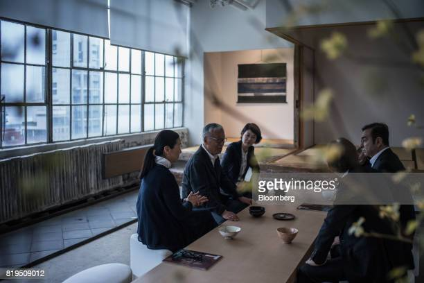 Carlos Ghosn chairman of Renault SAS Nissan Motor Co and Mitsubishi Motors Corp right sits with Japanese photographer Hiroshi Sugimoto center left at...