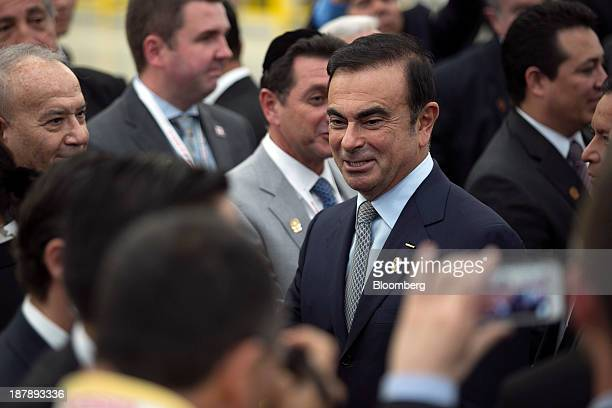 Carlos Ghosn chief executive officer of Nissan Motor Co center greets attendees during the opening ceremony for the new Nissan assembly plant in...