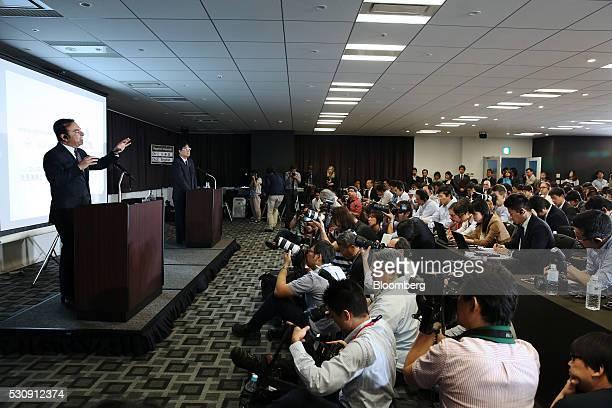 Carlos Ghosn chief executive officer of Nissan Motor Co left speaks as Osamu Masuko chairman and chief executive officer of Mitsubishi Motors Corp...