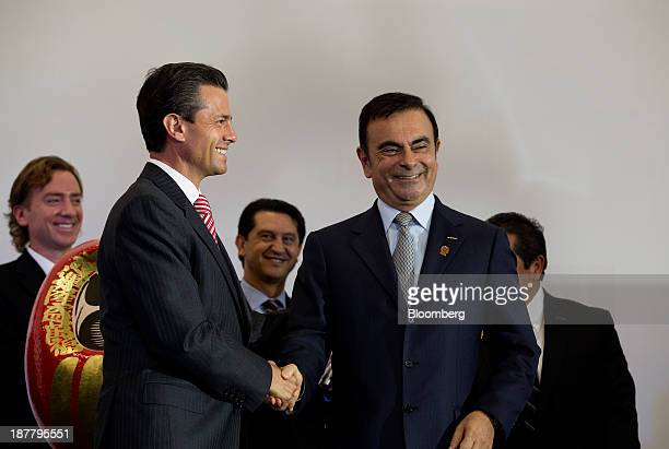 Carlos Ghosn chief executive officer of Nissan Motor Co right shakes hands with Enrique Pena Nieto Mexico's president during the opening ceremony for...