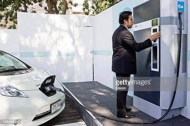 Carlos Ghosn recharge an electric car during the inauguration of the first quick charging station for electric vehicles in the fountain of Cibeles on...