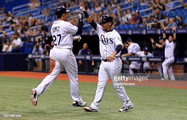 Carlos Gomez and Michael Perez of the Tampa Bay Rays high five after scoring a run in the second inning during a game against the Kansas City Royals...