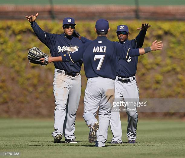 Carlos Gomez and Nyjer Morgan of the Milwaukee Brewers welcome Norichika Aoki to celebrate a win over the Chicago Cubs at Wrigley Field on April 11...