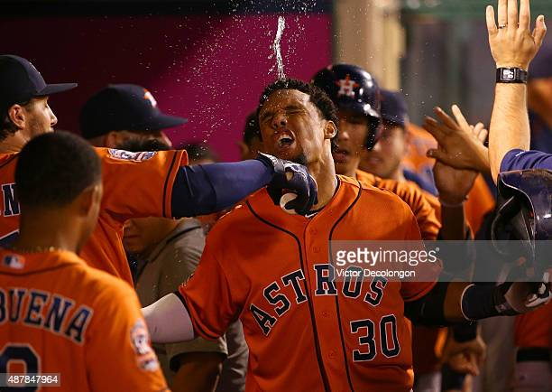 Carlos Gomez of the Houston Astros celebrates in the dugout as water is thrown on him by teammate Jake Marisnick after Gomez hit a tworun home run in...
