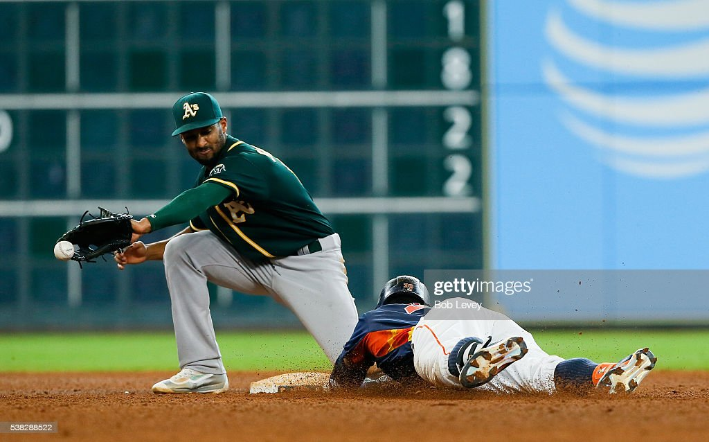 Carlos Gomez #30 of the Houston Astros doubles in the eighth inning as Marcus Semien #10 of the Oakland Athletics is late with the tag at Minute Maid Park on June 5, 2016 in Houston, Texas.