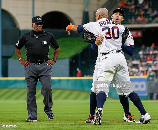 Carlos Gomez of the Houston Astros is held back by George Springer as he argues with umpire Laz Diaz as he took the field to start the 10th inning on...